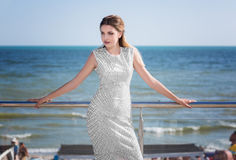Uma mulher modelo lindo em um vestido branco com testes padrões em um fundo do mar A senhora com cabelo escuro está em férias de  fotos de stock