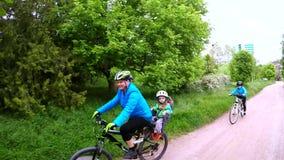 Uma mulher monta uma bicicleta e leva dentro o tronco de uma criança Movimento lento video estoque