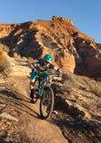 Uma mulher monta um Mountain bike abaixo da fuga de Jem abaixo do mesa da groselha no deserto do sul de Utá imagem de stock royalty free