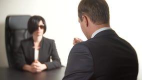 Uma mulher moreno em um terno faz perguntas a um homem em uma entrevista entrevista recruitment imagem de stock royalty free