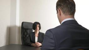 Uma mulher moreno em um terno faz perguntas a um homem em uma entrevista entrevista recruitment fotografia de stock royalty free