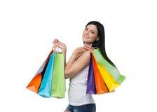 Uma mulher moreno feliz com os sacos de compras coloridos das lojas extravagantes Imagem de Stock