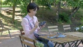 Uma mulher moreno fotografa seu saco em um smartphone video estoque