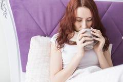 Uma mulher moreno nova atrativa senta-se em sua cama com uma caneca e os comprimidos Frios e tratamento da casa fotografia de stock