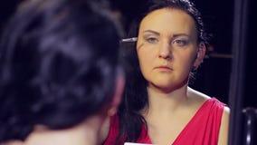 Uma mulher moreno nova em um vestido vermelho na frente de um espelho faz a composição do olho com máscaras claras com uma escova vídeos de arquivo