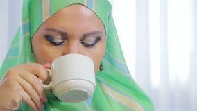 Uma mulher muçulmana nova em um lenço leve em um café come bolos e bebe o chá filme