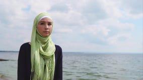 Uma mulher muçulmana nova em um véu vem com um olhar pensativo ao longo do mar filme