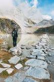 Uma mulher na frente de um lago montanhoso Fotos de Stock Royalty Free