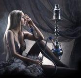Uma mulher na roupa interior erótica que fuma um cachimbo de água Fotografia de Stock Royalty Free