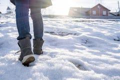 Uma mulher nas botas escala acima um monte coberto de neve, nos raios do sol da mola, contra o contexto das casas outing foto de stock royalty free