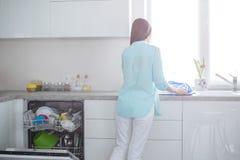 Uma mulher nas calças de brim brancas e em uma camisa de turquesa está com ela para trás ao lado de uma máquina de lavar louça ab imagens de stock royalty free