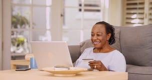 Uma mulher negra mais idosa paga-lhe contas em seu portátil Foto de Stock