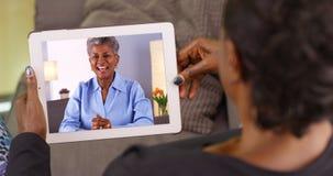 Uma mulher negra mais idosa que fala a seu amigo através do bate-papo video imagem de stock