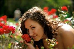 Uma mulher no jardim de rosas vermelho fotos de stock royalty free
