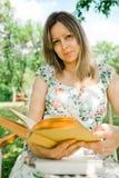 Uma mulher no livro de leitura do vestido da flor e assento exterior fotos de stock royalty free