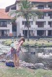 Uma mulher no pareo alimenta gansos e ganso cinzentos da retardação no lago perto do hotel de luxo em DUA de Nusa, ilha tropical  Imagem de Stock
