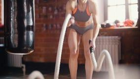 Uma mulher no treinamento no gym Treinando suas mãos com batida das cordas filme