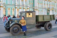 Uma mulher no uniforme durante a segunda guerra mundial inclinou-se no carro ZIS sobre Imagem de Stock