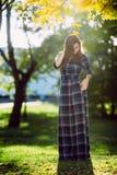 Uma mulher no vestido quadriculado longo Parque romântico da menina na primavera Uma mulher anda no parque em um vestido ocasiona Fotos de Stock Royalty Free