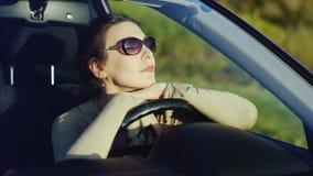 Uma mulher nos óculos de sol relaxa no carro Senta-se atrás da roda, admirando o cenário bonito no por do sol Excitador feliz filme