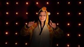 Uma mulher nos pijamas sob a forma de um girafa, dança de umas crianças brilhantes retrato emocional de um estudante trajado vídeos de arquivo