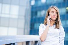 Uma mulher nova bonita do mediador imobiliário no telefone Foto de Stock