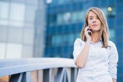 Uma mulher nova bonita do mediador imobiliário no telefone Imagens de Stock Royalty Free