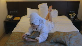 Uma mulher nova, bonita em um revestimento branco senta-se em uma cama em um hotel, quarto e escreve-se uma mensagem de SMS no te filme