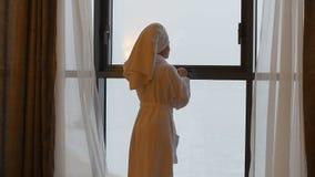 Uma mulher nova, bonita em um revestimento branco vem à janela, abre as cortinas e os olhares nele video estoque