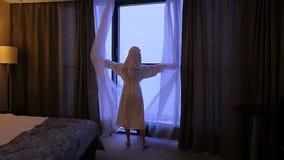 Uma mulher nova, bonita em um revestimento branco vem à janela, abre as cortinas e os olhares nele Movimento lento filme