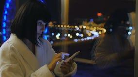 Uma mulher nova, bonita em uma veste branca senta-se pela janela, olha-se no telefone e escreve-se uma mensagem de SMS Do vídeos de arquivo