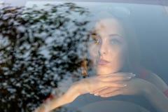Uma mulher nova, bonita senta-se na roda do carro e olhada dreamingly com o brilho do para-brisa dianteiro fotografia de stock