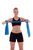 Uma mulher nova com uma faixa do estiramento Imagens de Stock
