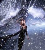 Uma mulher nova em um vestido escuro na seda de sopro imagens de stock royalty free