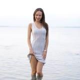 Uma mulher nova em um vestido está estando na água fotografia de stock royalty free