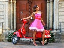 Uma mulher nova em um vestido que levanta perto de um 'trotinette' foto de stock