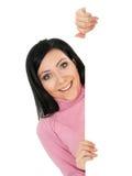 Uma mulher nova está escondendo atrás de uma parede branca Imagens de Stock Royalty Free