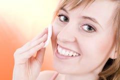 Uma mulher nova está tomando de sua pele Imagem de Stock Royalty Free