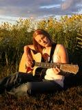 Uma mulher nova joga uma guitarra Imagem de Stock Royalty Free