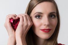 Uma mulher nova que dá forma a um coração com suas mãos Fotos de Stock
