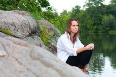 Uma mulher nova só que senta-se em rochas no rio Imagens de Stock