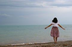 Uma mulher nova sozinho no beira-mar Fotografia de Stock