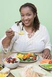 Uma mulher obeso que come o alimento Fotografia de Stock Royalty Free