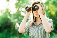 Uma mulher olha através dos binóculos exteriores na floresta fotografia de stock