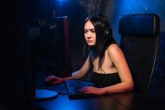 Uma mulher olha a câmera ao sentar-se na frente de seu PC e ao jogar jogos de computador em linha e ao fluir o jogo no fotos de stock