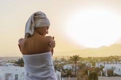 Uma mulher olha o sol de ajuste com uma toalha em sua cabeça após um chuveiro em um terraço que negligencia as montanhas Imagem de Stock