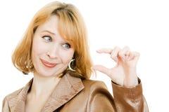 Uma mulher olha um objeto pequeno em sua mão Fotos de Stock