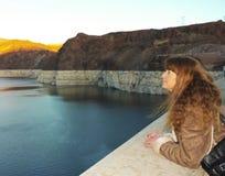 Uma mulher olha um por do sol sobre o hidromel do lago Fotografia de Stock Royalty Free