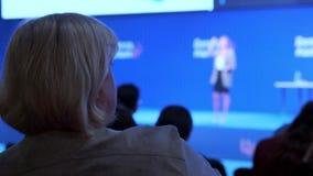 Uma mulher olha um seminário e escuta o orador Discuta o conceito do desenvolvimento econômico e das novas tecnologias filme