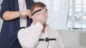 Uma mulher põe o homem sobre o teste de detector de mentira dos sensores video estoque